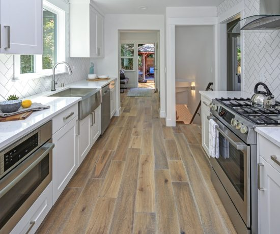 Remodeled kitchen room with white cabinets, marble countertops, herringbone backsplash and wide-plank hardwood floors.